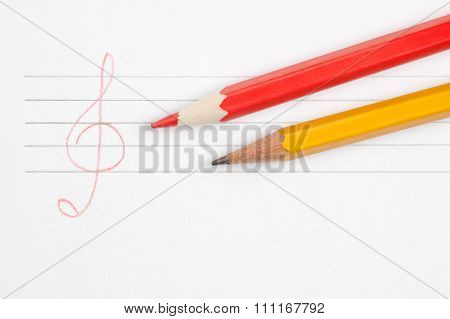 White paper sheet with two pencils and hand drawn stave and treble clef top view have place for text