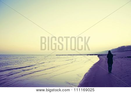 Lonely Woman Walking On The Beach.