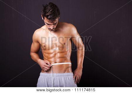 Fit man measuring his waist on grunge background