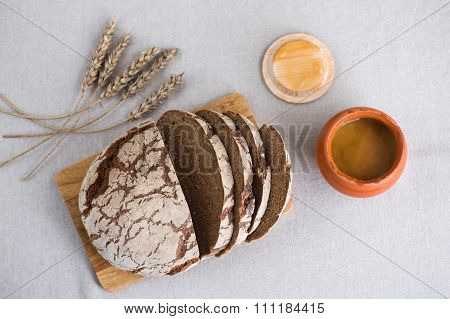 Tasty And Delicious Sliced Loaf Of Bread On A Board. Bread Is On A Background Of Linen Fabric. Next