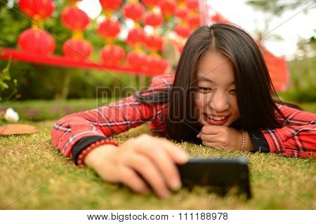 Chinese woman use smartphone in the park during chinese new year
