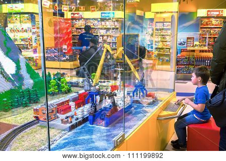 Moscow, Russia - December 11, 2015: Little Boy Looking At The Sea Port Made By Lego Blocks In Centra