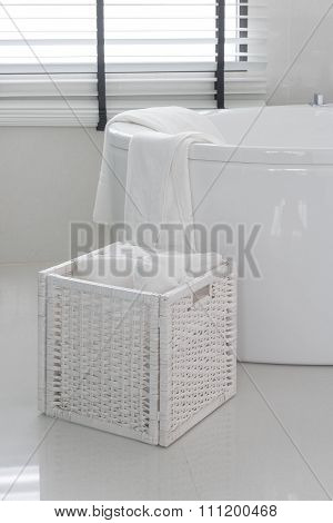 White Towel In Wooden Basket With Modern Bath Tub