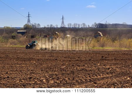 View Of Tractor Sowing In Field In Early Spring
