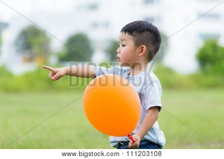Little kid hald with the balloon and finger point aside