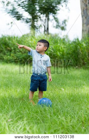 Little kid play soccer ball and finger point aside