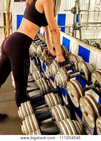 Body part of woman  working with  dumbbells his body at gym.