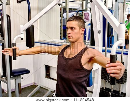 Portrait of man working his arms on training apparatus at gym.