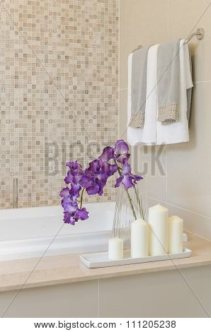 Glass Vase Of Flower On Bath Tub With Towel Hanging