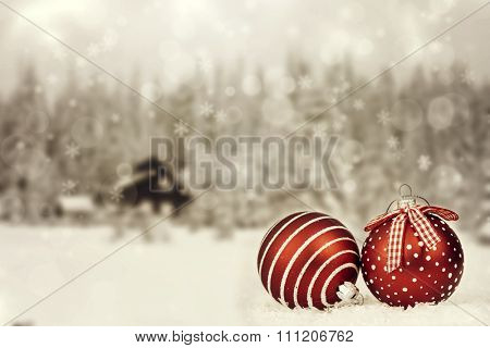 Red Christmas decorations in front of snow cowered pine trees