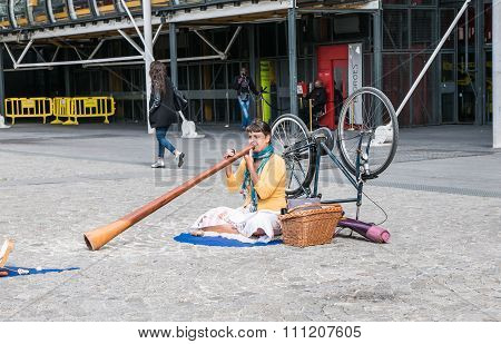 Young Woman Plays Didgeridoo On Centre Pompidou Plaza, Paris
