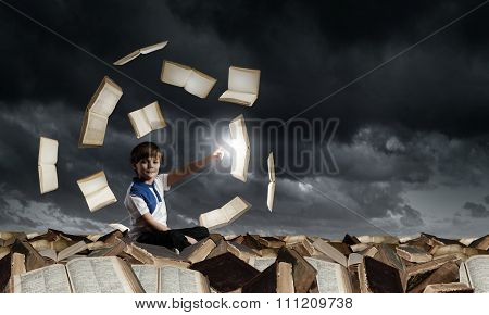 Little cute boy sitting on pile of books and pointing with finger