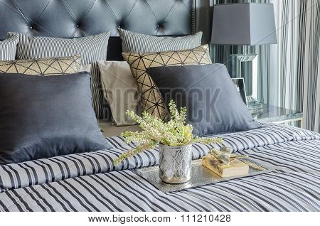 Tray Of Book With Vase Of  Plant On Bed In Luxury Black Bedroom
