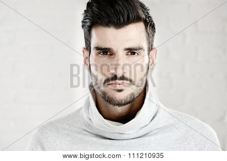 Portrait photo of cool handsome young man looking at camera, white background.