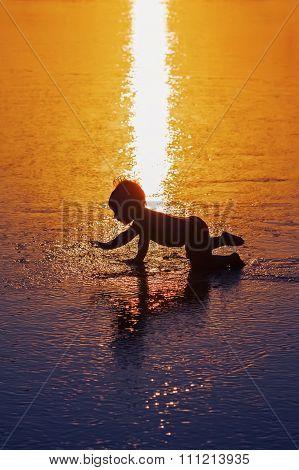 Black Silhouette Of Little Child On Wet Sunset Beach