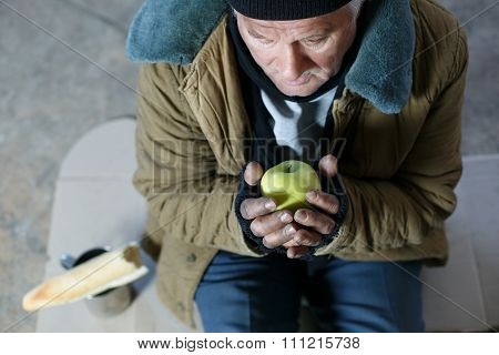Senior homeless man holding an apple.