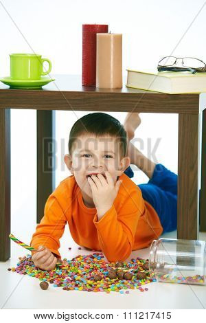 Naughty little kid eating sweets under table. Smiling, isolated on white, lollipop in hand.