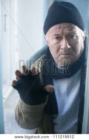 Homeless man looks out of the window.