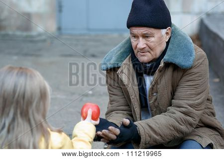 Little girl gives apple to the beggar.