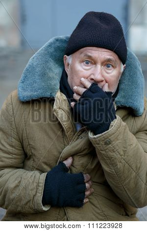 Homeless senior-aged man looks startled an alarmed.
