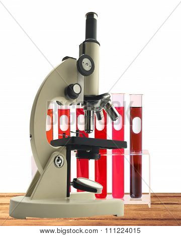 Laboratory Metal Microscope And Test Tubes With Blood In Holder On Wooden Table Isolated On White Ba