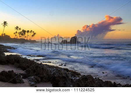 Sunrise At A Rocky Beach With Purple Clouds