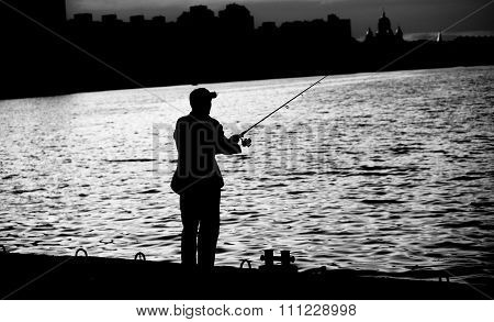 Fisherman Standing On Edge Of Dock With Fishing Rod Near River In City Black And White