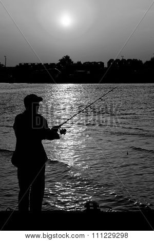 Fisherman Standing On Edge Of Dock With Fishing Rod Near River And Beach Town In Rays Of Sunset Blac