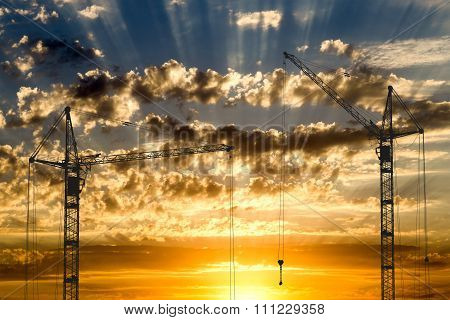 Hoisting Cranes Working On Beautiful Cloudy Sky With Golden Sunset And Rays Of Light Background