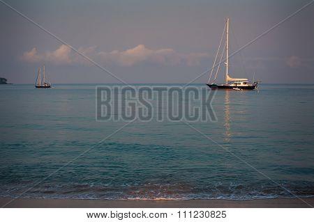 Yachts In Azure Sea Near Beach Against Blue Sky