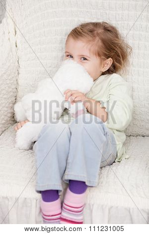 Cheerful female child is playing with fluffy toy