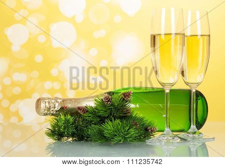 Two glasses of champagne with bottle on yellow New Year back