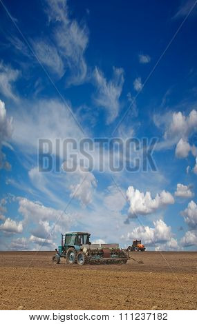 Tractors Cultivating Field