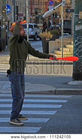 street juggler is performing on the intersection in Milan, Italy