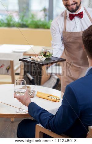 Skillful male cafe worker brings the order of client