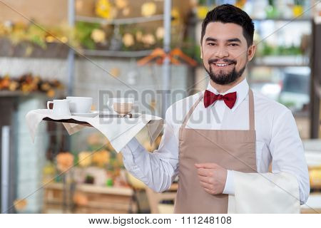 Handsome male cafe worker is serving a customer