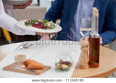 Cheerful male cafe worker is serving a client