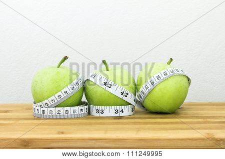 Green Apple With Measuring Tape On Wooden Plate With Concrete Background In Concept Of Healthy And D