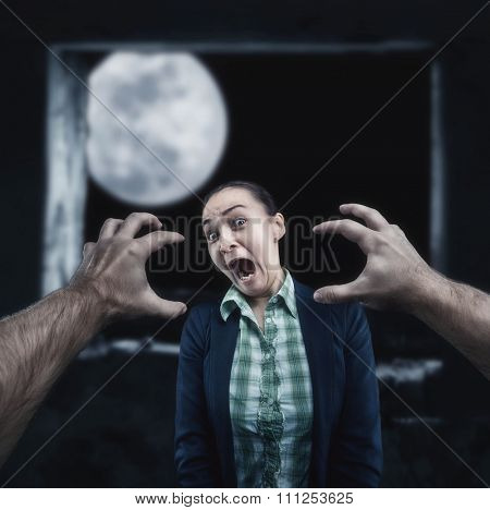 Young woman frightened with huge human hands in the night