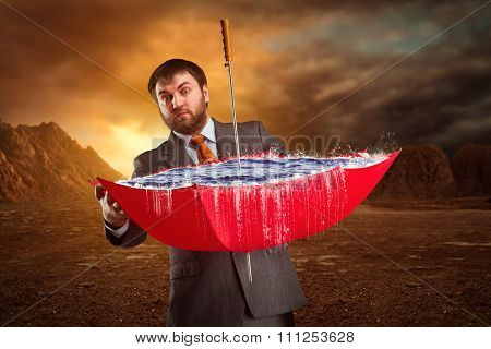 Businessman with red umbrella full of water at night