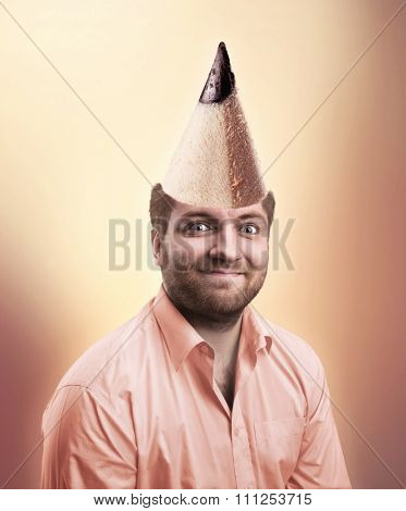 Smiling man wearing pink shirt with pencil cone on the head
