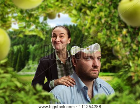 Businesswoman is eating businessman's head as an apple in the garden