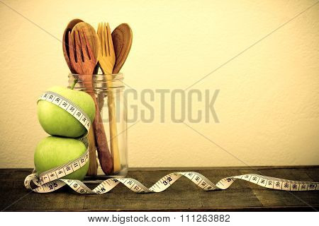Green Apple With Measuring Tape And Wooden Spoon And Fork On Wooden Table And Concrete Wall Backgrou