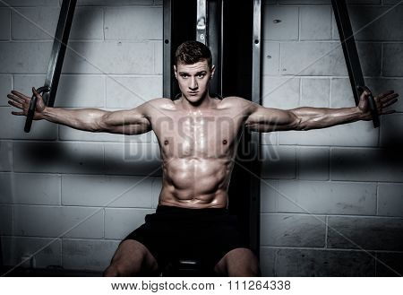 Athletic man doing exercises on training apparatus at the gym's studio