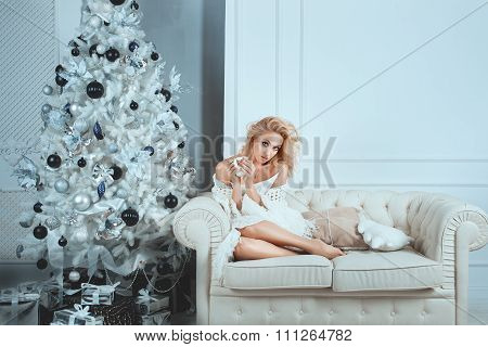 Cute Girl Sitting On White Sofa Near The Christmas Tree.