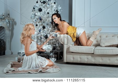Girls Give Gifts To Each Other Under The Christmas Tree.
