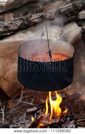 Pot With Soup Cooking On Campfire