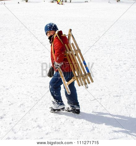 Young Boy Sledding Down The Hill In Snow, White Winter