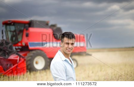 Businessman In Soybean Field. Combine Harvester In Background