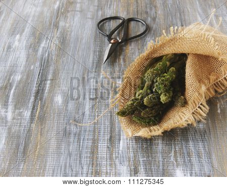 asparagus in a canvas bag with pair of scissors on wooden table, selective focus